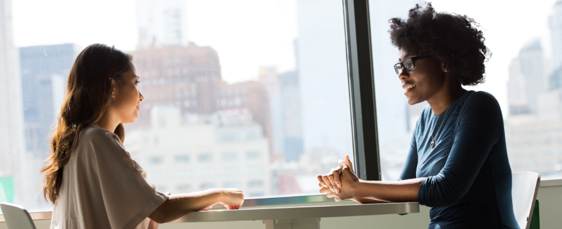 Two professional women discuss at a table in a business setting.